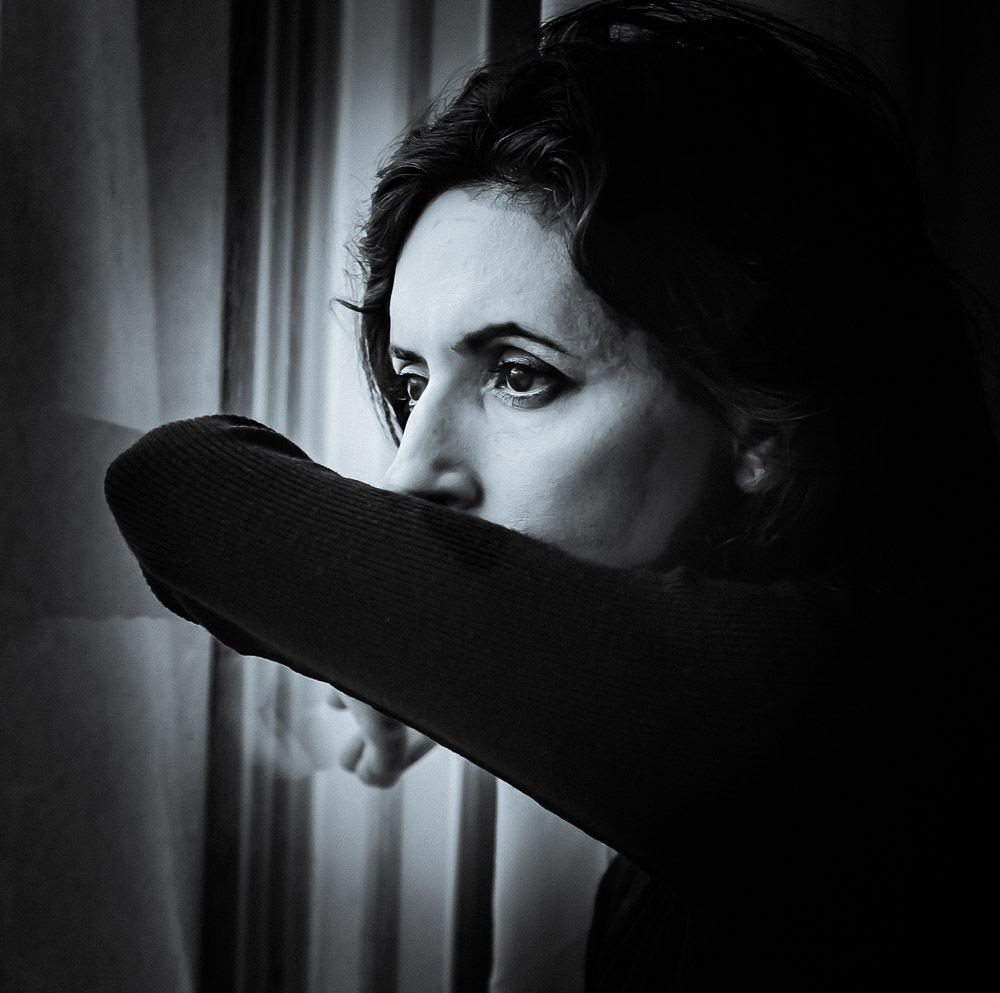 beautiful woman stands in front of the window Sadness overwhelms